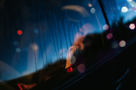 Woman unfocused through the window car with drops