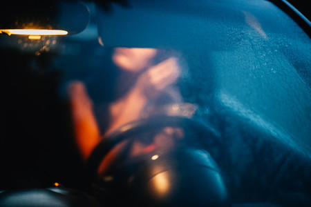 Unfocused young woman puts on makeup inside a car at sunset