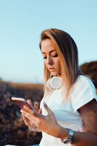 Young woman taken notes on her smartphone in the field