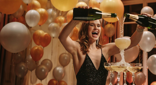 Excited woman filling up pyramid of champagne