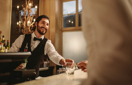 Bartender serving drinks to guest at a party