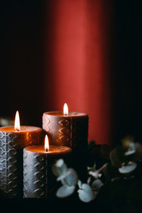 Black burning candles against dark red background with eucalyptus branch