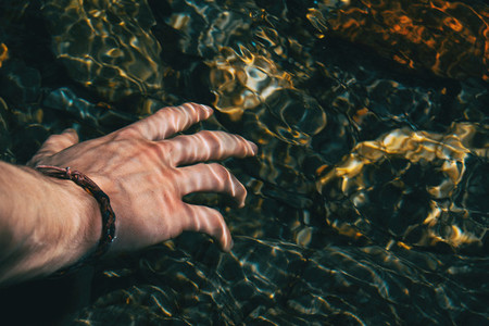 Close up of a hand touching the surface of the water with light reflections