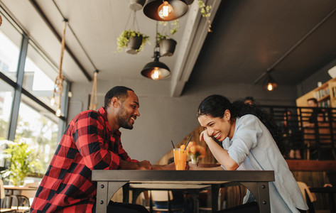 Couple in love smiling at a coffee shop