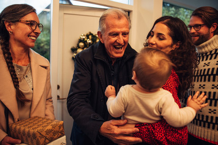 Family welcoming grandparents for christmas eve celebrations