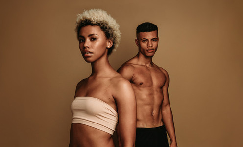 African american man and woman standing on brown background