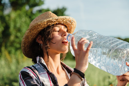 Farmer woman drinking water from plastic bottle during harvesting
