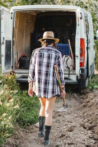 Farmer woman walking to her van at crop field