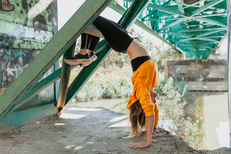 Woman does contortionism on an abandoned bridge