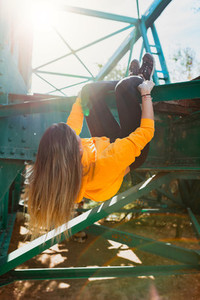 Woman hanging like a monkey from iron beams  Freedom concept