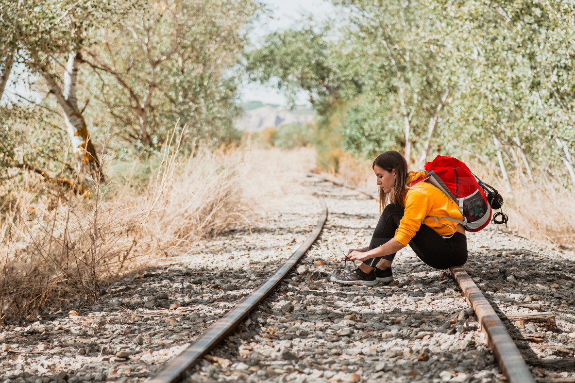 Woman tying shoelaces on sneakers sitting on the train tracks