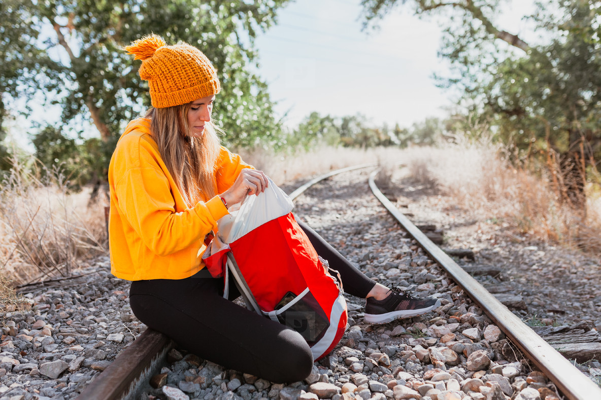 Woman trekking rests on an abandoned railway track looking for something in her backpack