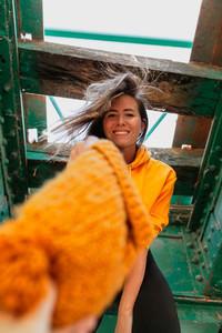 Woman exploring an old railway bridge hands over her wool cap