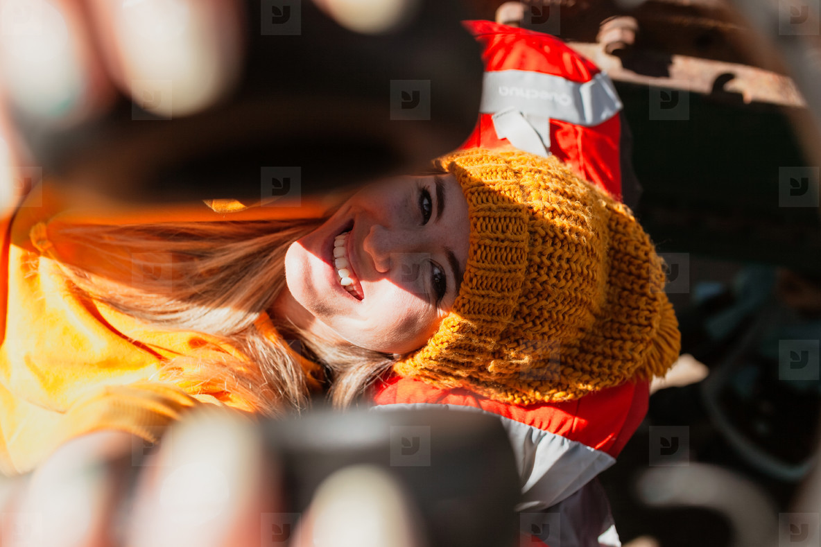 Smiling woman lying on abandoned railroad tracks rests