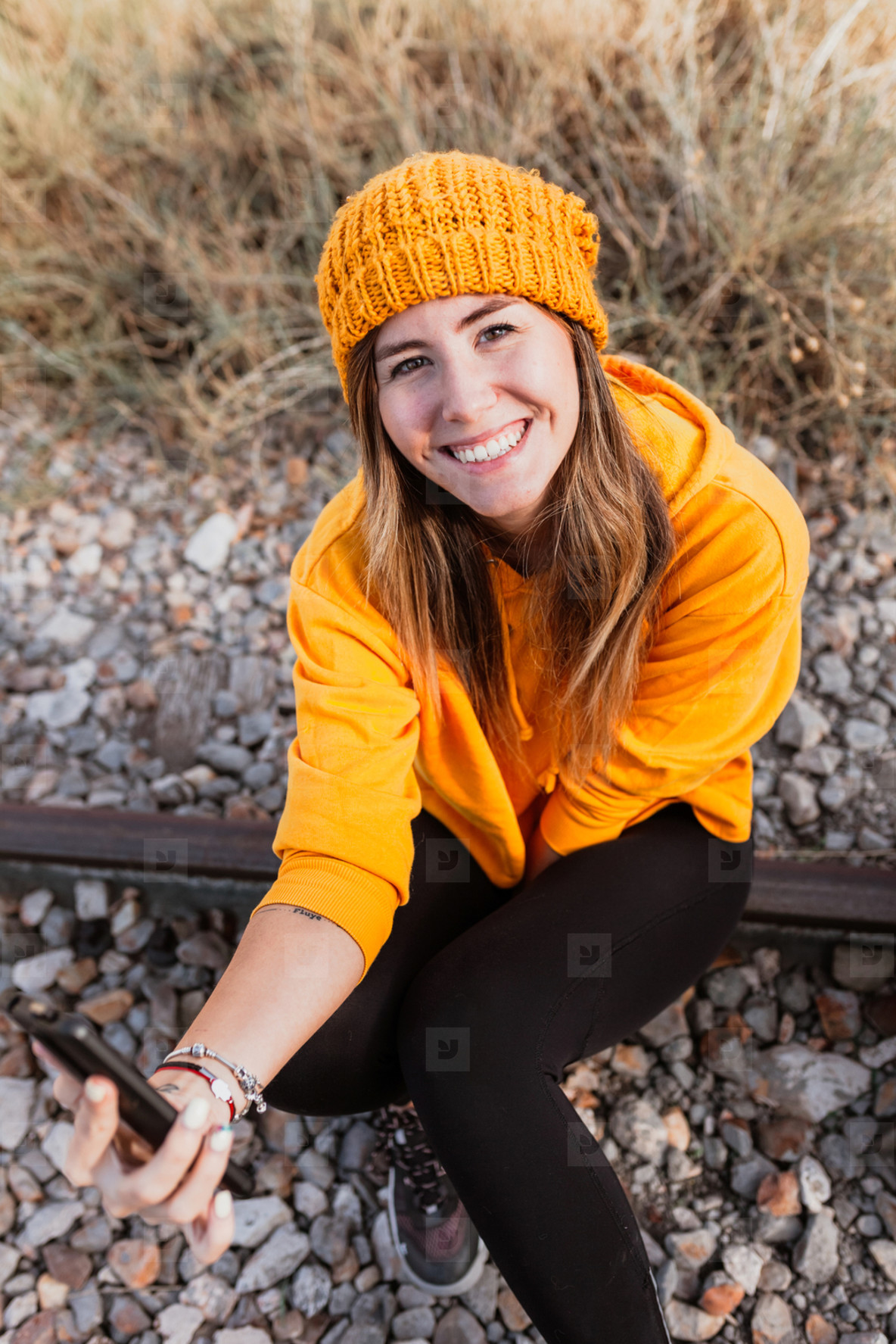Woman using her smartphone on an abandoned railroad track