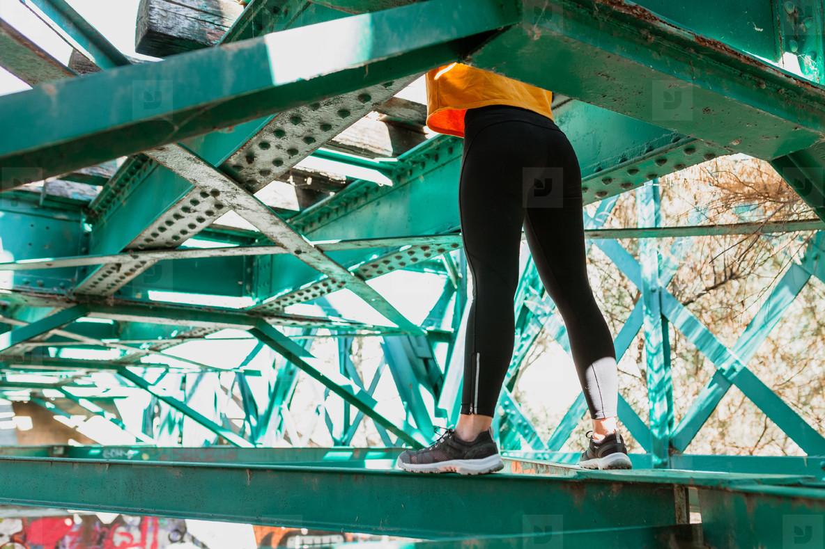 Woman has fun exploring an old  abandoned iron railroad bridge