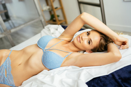 Caucasian blonde girl posing in blue bra and jeans lying on the bed
