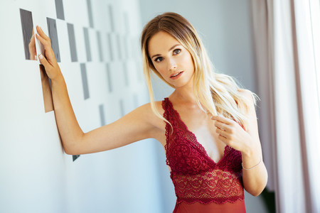 Caucasian woman in red lingerie posing in the hallway of her home