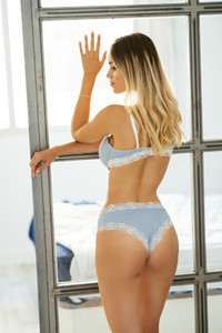 Caucasian girl in blue lingerie leaning against a window in her living room