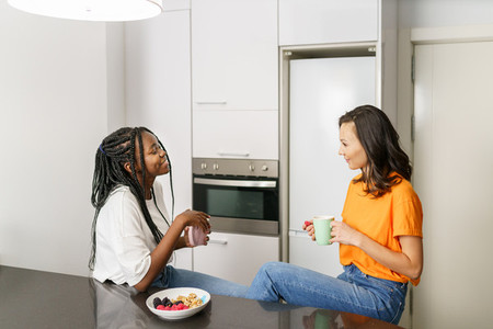 Two friends having a healthy snack while chatting at home