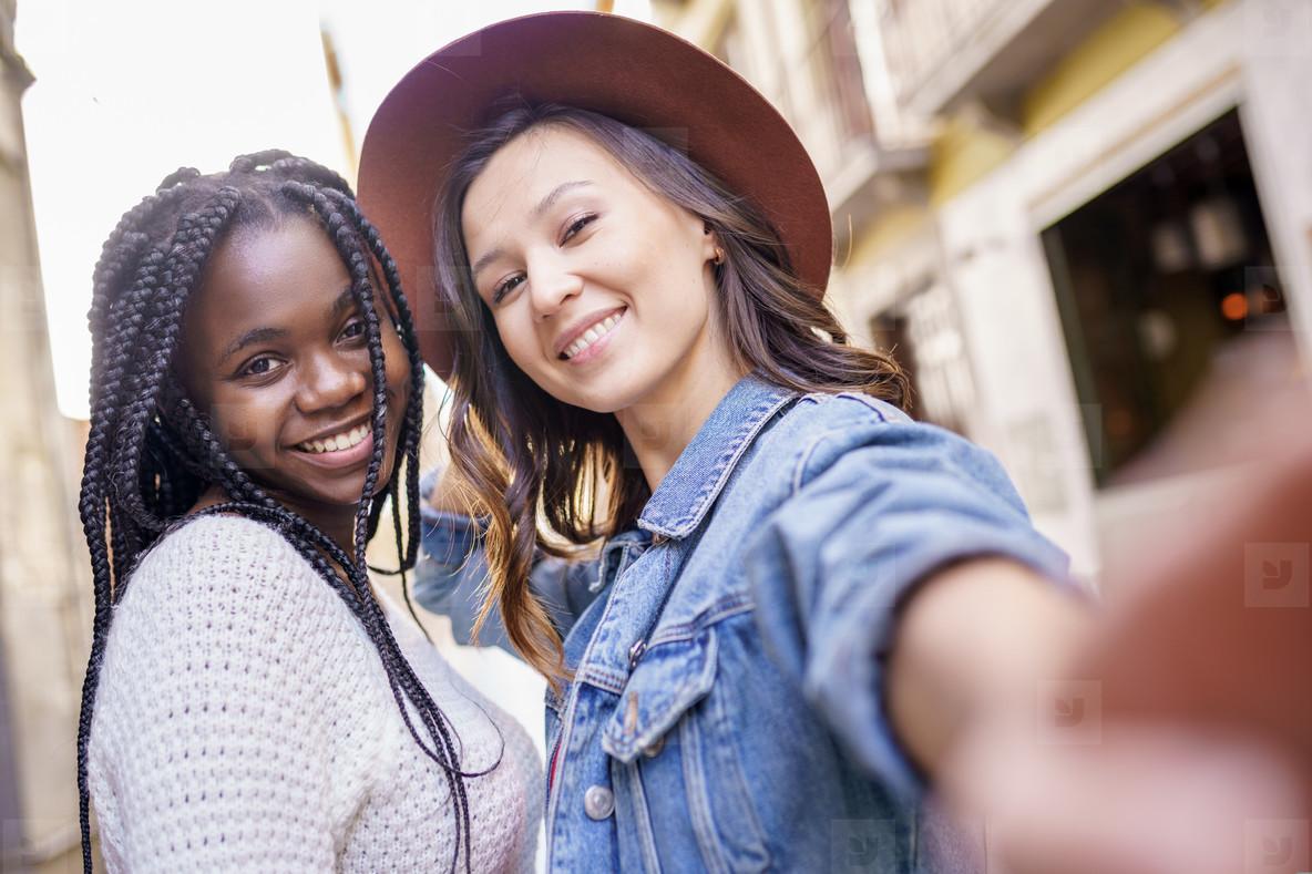Two beautiful multiethnic women making selfie and grimacing