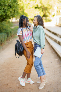 Two multiethnic women posing together with colorful casual clothing