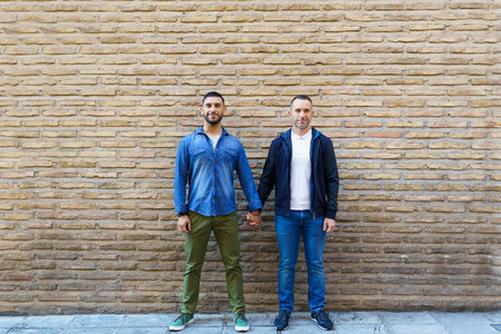 Gay couple holding hands posing in front of a brick wall