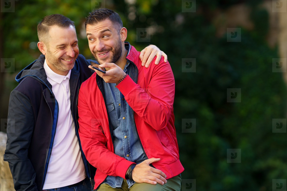 Gay couple recording a voice note together on their smartphone