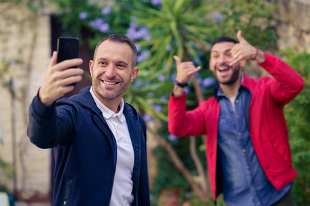 Gay couple making a funny selfie with their smartphone