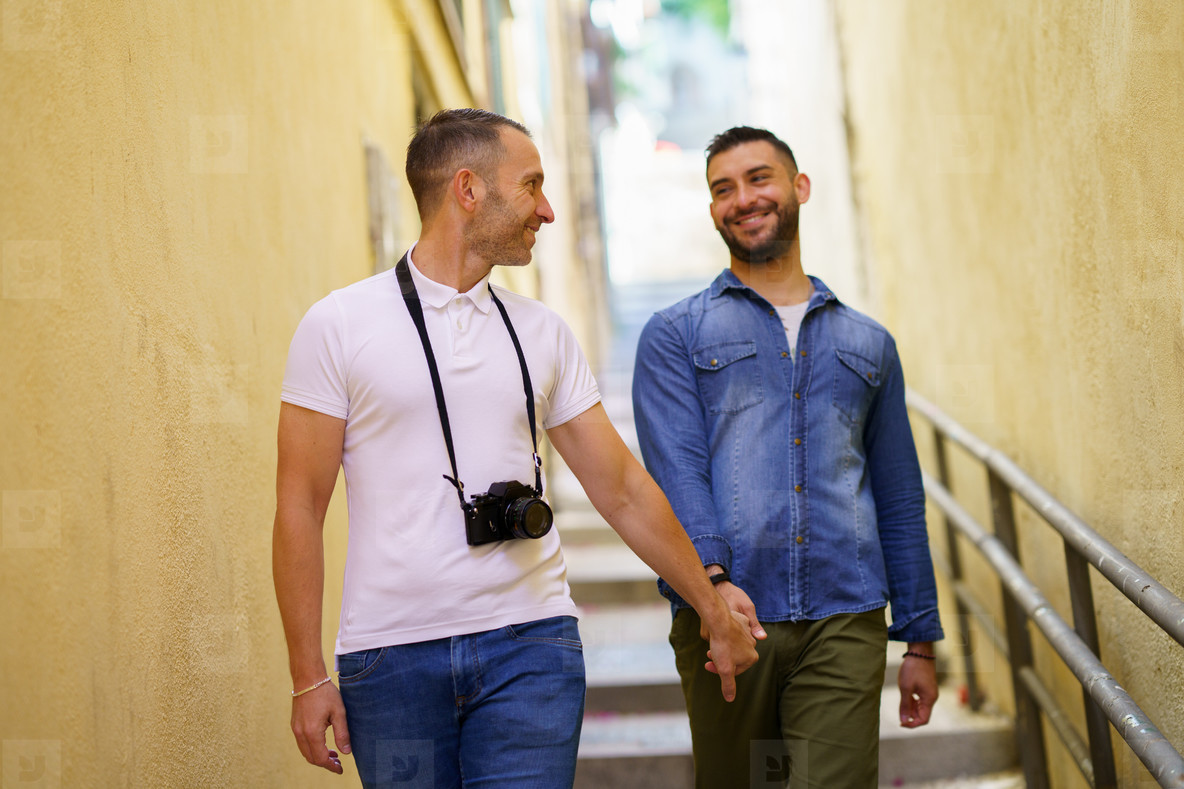 Gay couple tourists walking hand in hand on the street