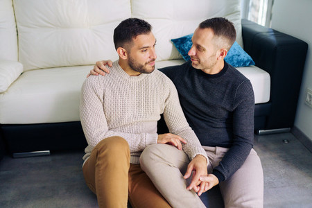 Gay couple sitting near the couch at home in a romantic moment