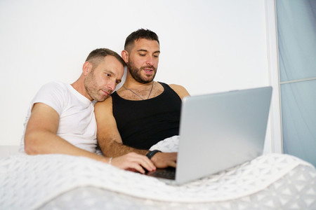 Gay couple consulting something on their laptop while lying on the bed