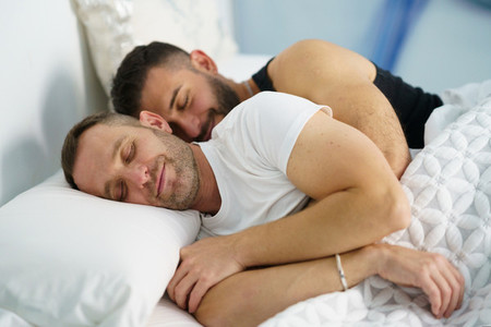 Gay couple sleeping in each others arms