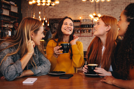 Happy young friends meeting in a coffee shop