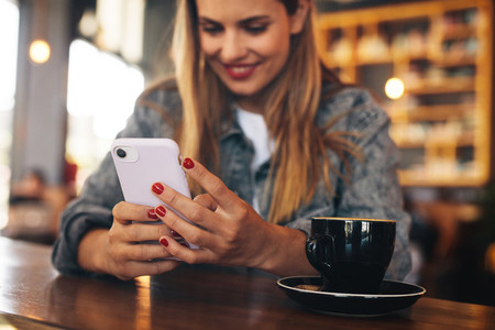Woman using her mobile phone at a coffee shop
