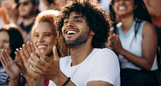 Smiling man watching a soccer match at stadium