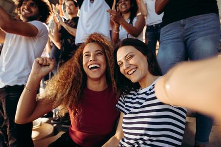Excited female spectators making a selfie at stadium