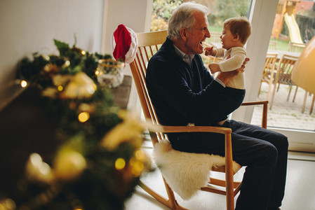 Grandfather playing with grandson during christmas