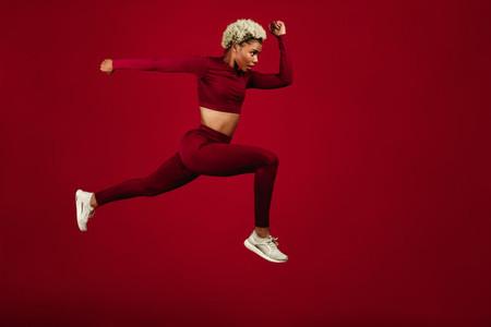 Female sprinter running on maroon background
