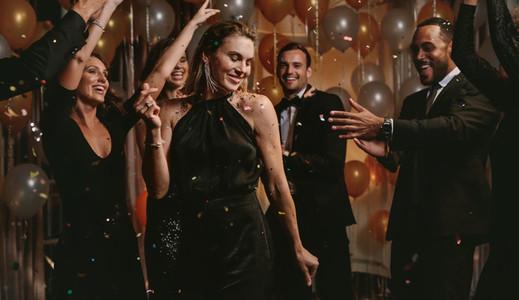 Beautiful woman dancing with friends at gala night