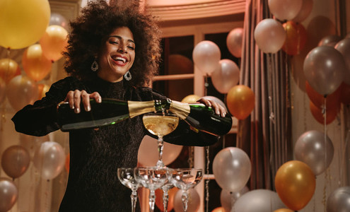 Beautiful woman filling pyramid of glasses with champagne