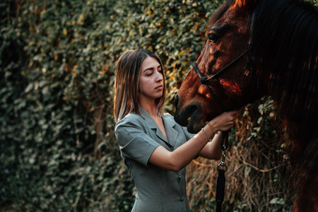 A woman caressing and talking to his horse in the countryside