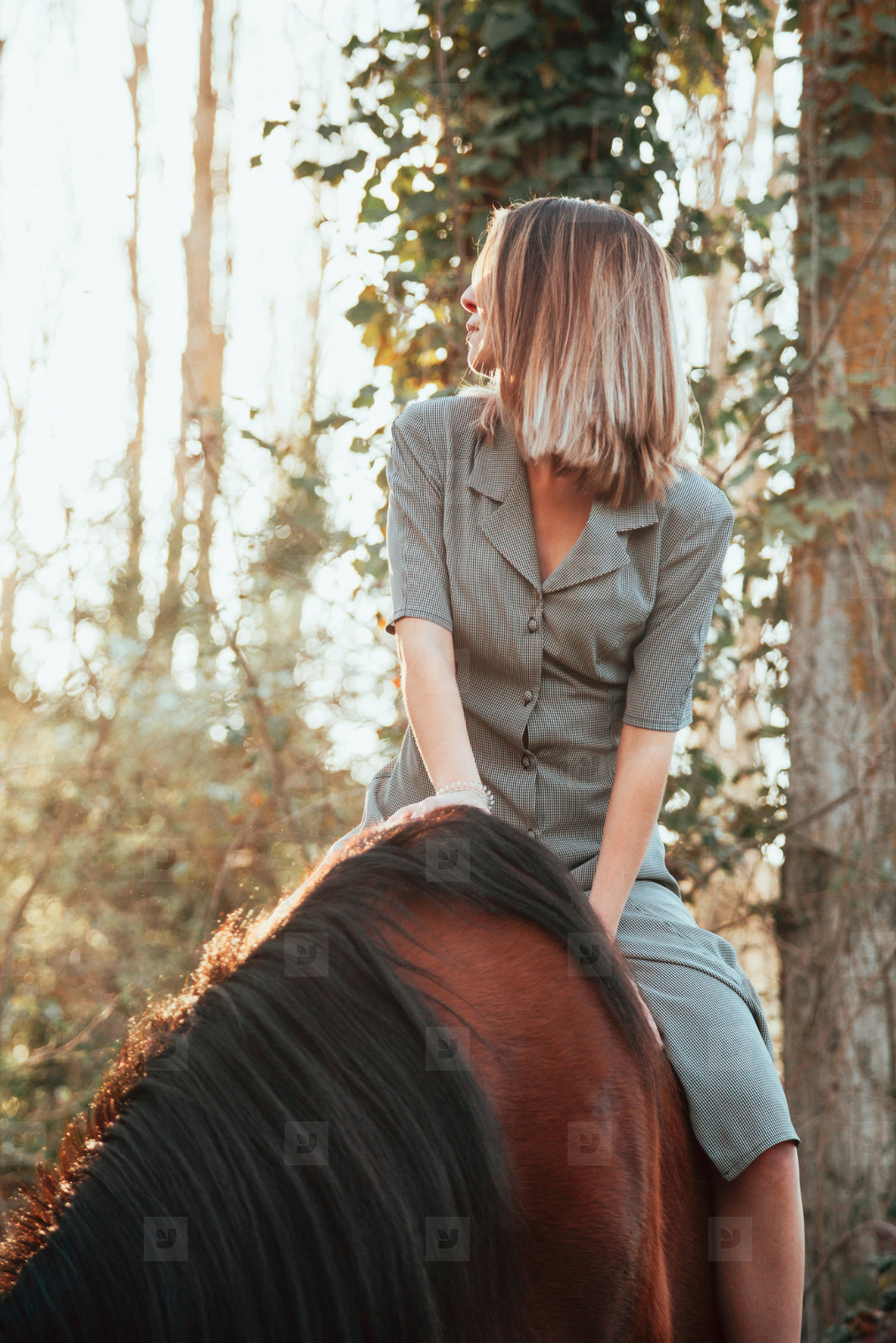 Beautiful young woman riding her brown horse and wearing dress