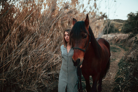 An elegant woman in a dress who walks her horse along a path