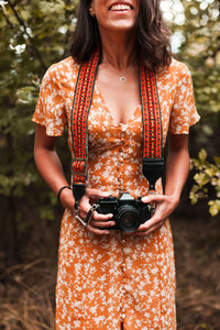 Girl photographer in the woods holds in her hand an old vintage film camera