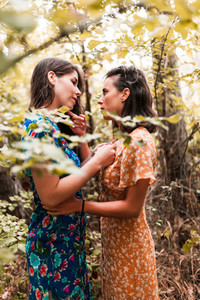Two young lesbians caressing each other in the woods