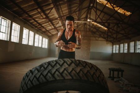 Fit woman doing tire flip workout