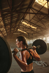 Woman doing squats workout in old warehouse