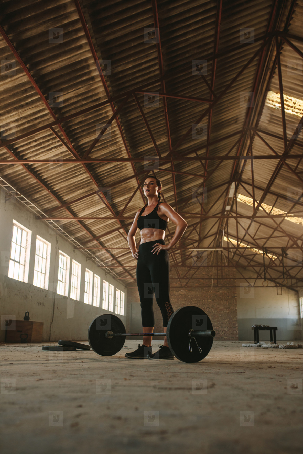 Woman taking break from weight lifting workout