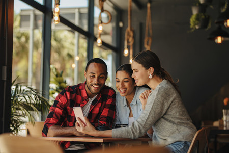 Woman sharing pictures with friends at cafe